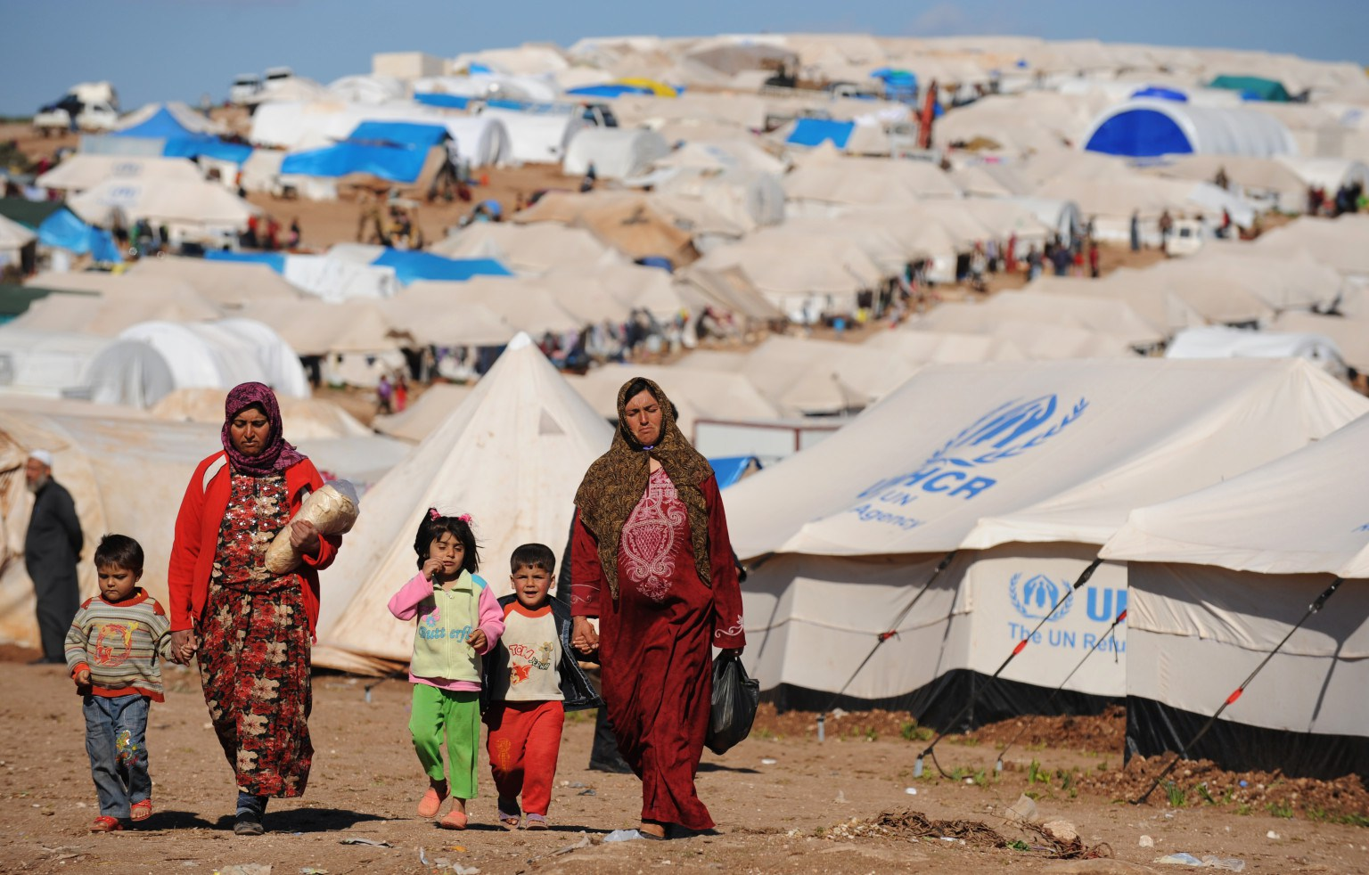 Syrian internally displaced people walk in the Atme camp, along the Turkish border in the northwestern Syrian province of Idlib, on March 19, 2013. The conflict in Syria between rebel forces and pro-government troops has killed at least 70,000 people, and forced more than one million Syrians to seek refuge abroad. AFP PHOTO/BULENT KILIC        (Photo credit should read BULENT KILIC/AFP/Getty Images)