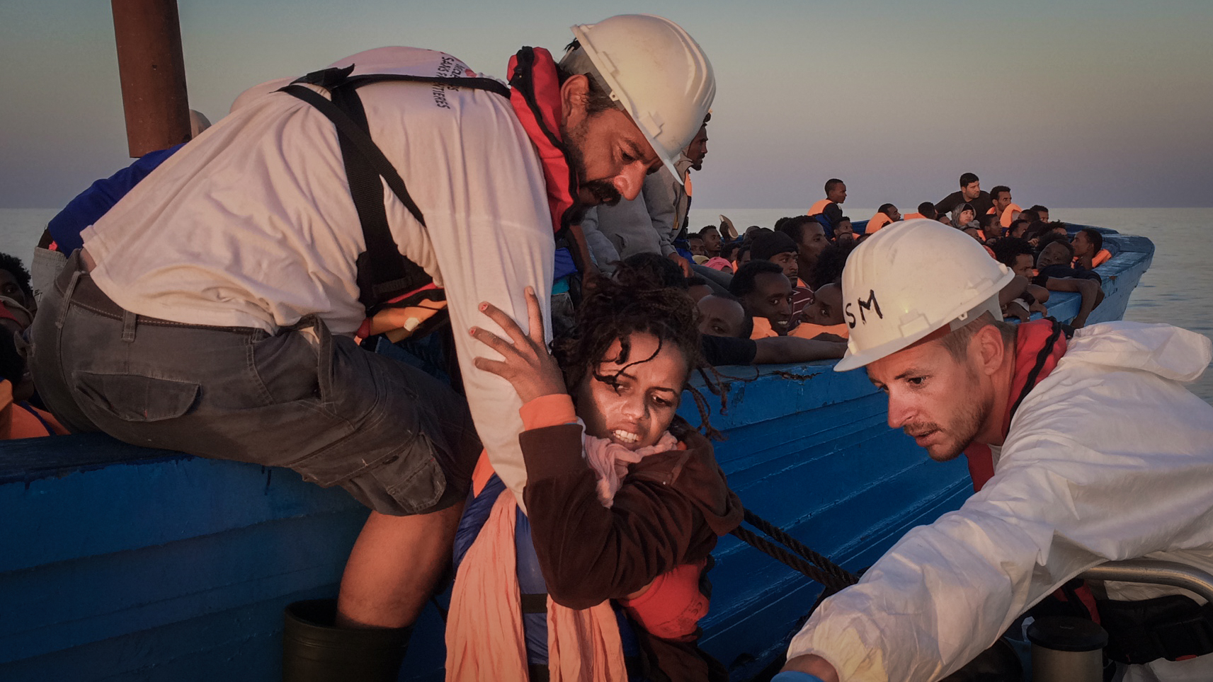 A woman is being helped from a wooden boat carrying around 350 people to an MSF rig that will bring her on board Dignity.